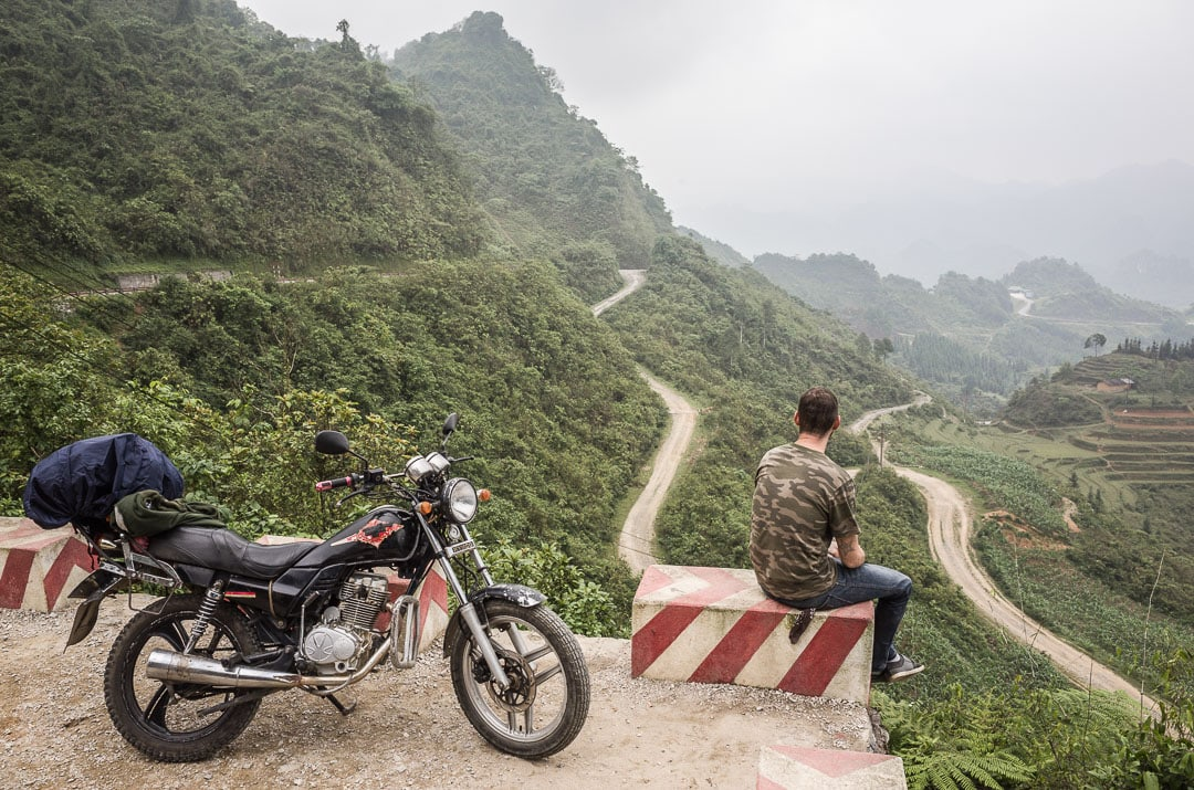 A man sits in a camoflauge t-shirt to take in scenic views by his motorcycle near Fairy Bosom lookout in Ha Giang, Vietnam. How to ride the most epic motorcycle loop in Vietnam
