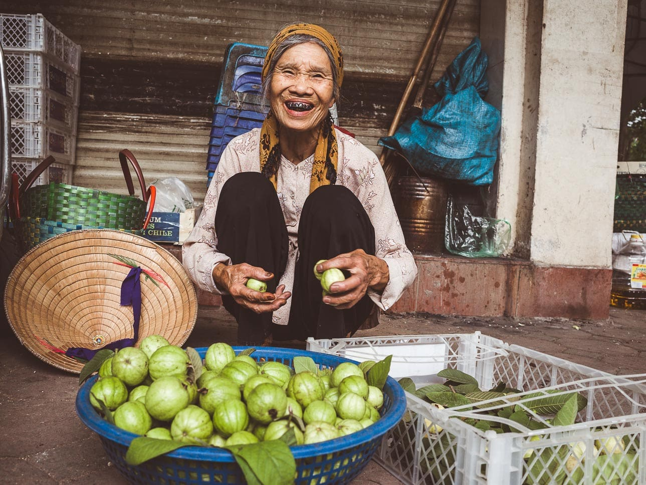 A smiling woman sells guava on the street in Hanoi, Vietnam