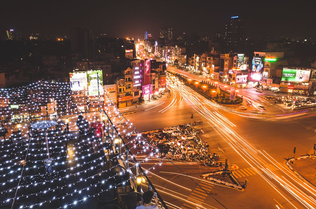 A long exposure of Hanoi traffic at night from a rooftop cafe