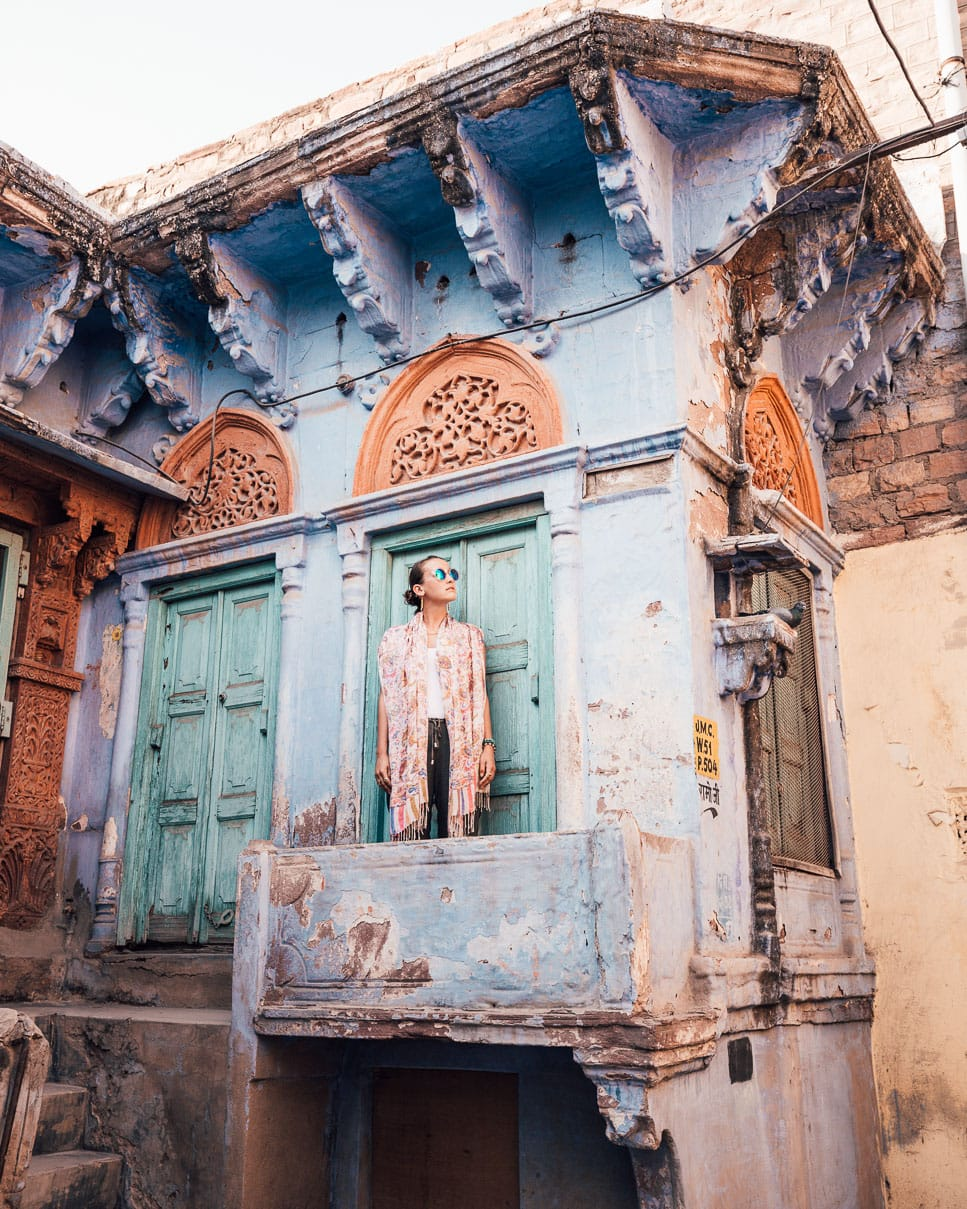 Sindhya Co-founder of Why We Seek in front of a blue home in Jodhpur, India.