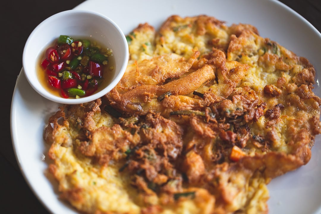 Khai Jiaow also known as a Thai omelette sits on a plate with Nam Pla Prik dipping sauce