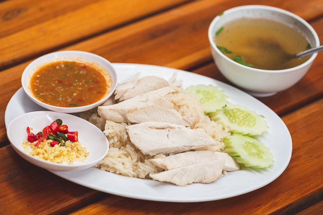 A plate of Khao Man Gai - Thai chicken rice in Bangkok, Thailand with soup
