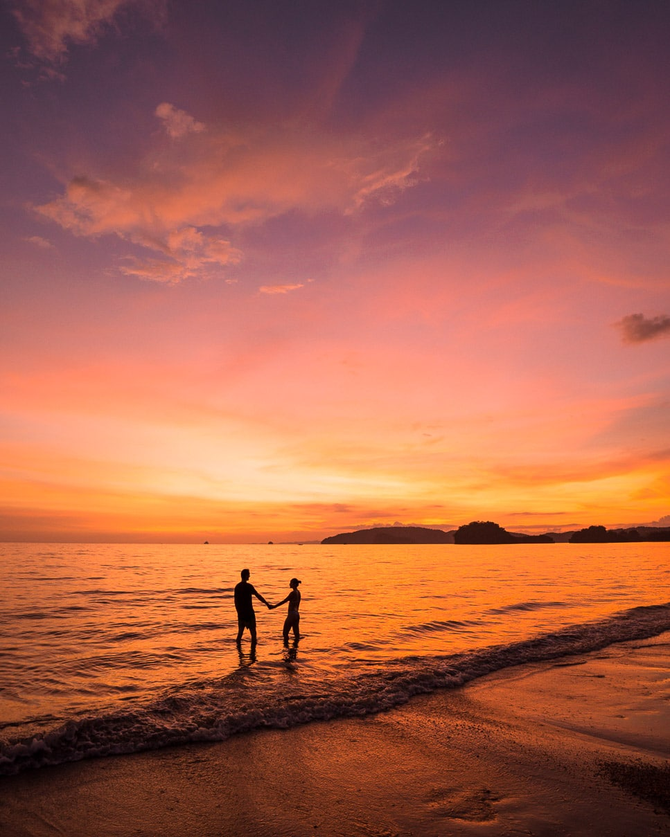Silhouette of a couple holding hands at sunset on Nopparat Thara beach in Krabi, Thailand