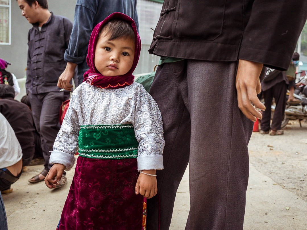 A young girl with her father at the Dong Van Market in Ha Giang, Vietnam on Sunday