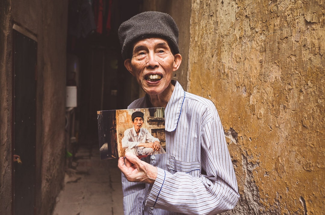 A one hundred year old man holding a picture of himself near his home in Hanoi