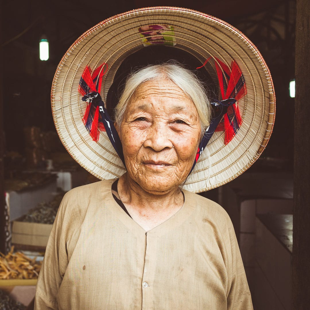 A portrait of a local woman in a conical hat at Dong Xuan market in Hanoi, Vietnam