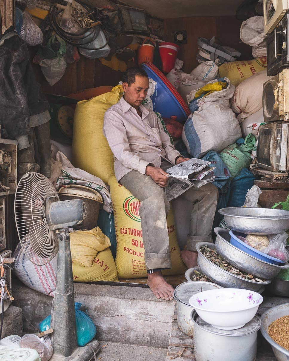 A man reads the newspaper and takes a break in his rice flour shop in Hanoi