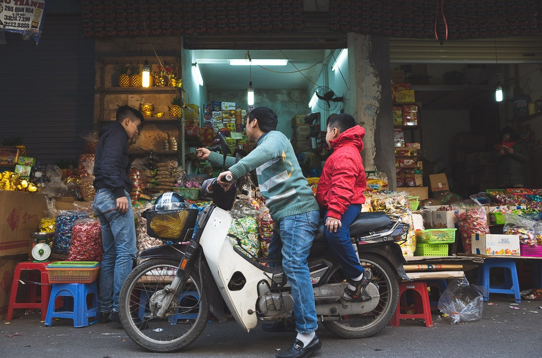 A man shopping with his son on a motorbike in Hanoi, Vietnam