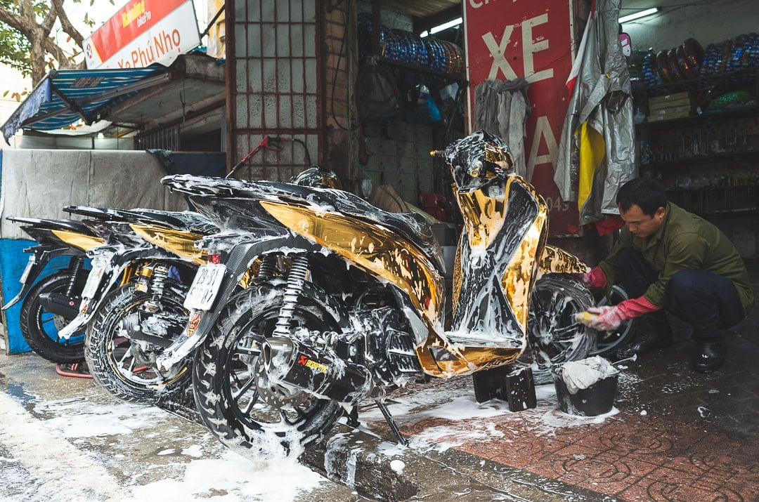 A man washes motorbikes in Hanoi, Vietnam
