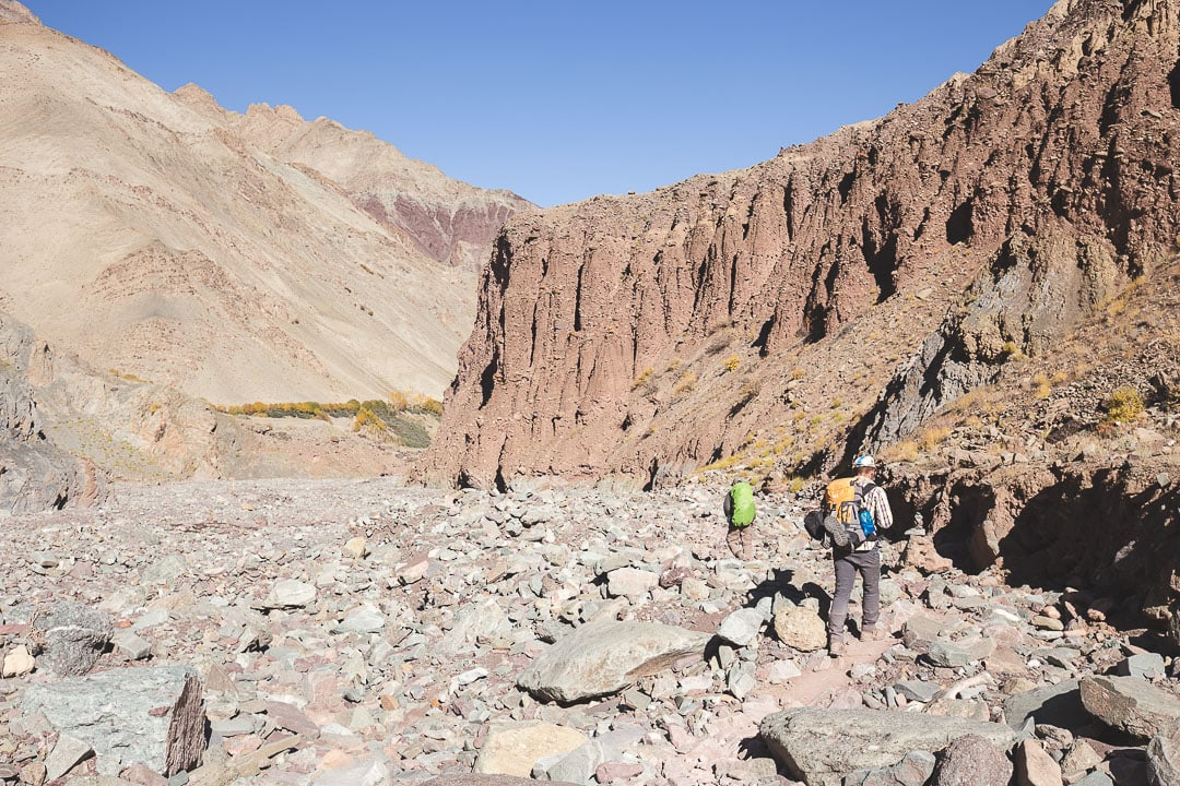 Two trekkers walk along a dry river bed on the Markha Valley trek