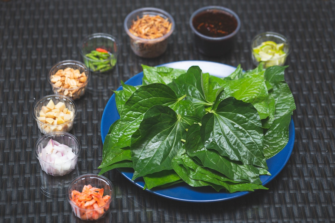 Miang Kham a royal Thai food is set out on a table to be rolled into leaves and eaten
