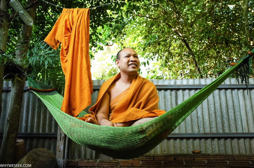 A Buddhist monk in an orange robe sits in his hammock at Wat Umong temple in Chiang Mai, Thailand