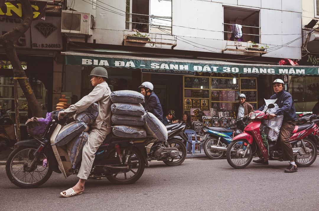A few motorbikers carrying goods sit and wait on their bikes in the old quarter of Hanoi, Vietnam