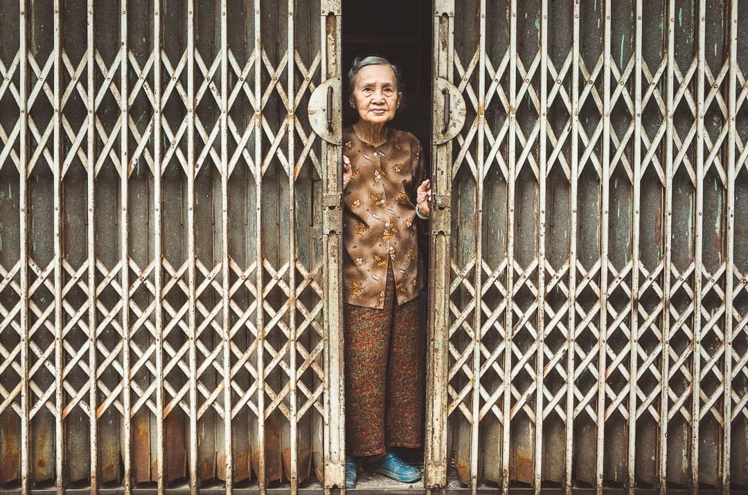 A shopkeeper peeks out from behind her gate in the Old Quarter in Hanoi, Vietnam