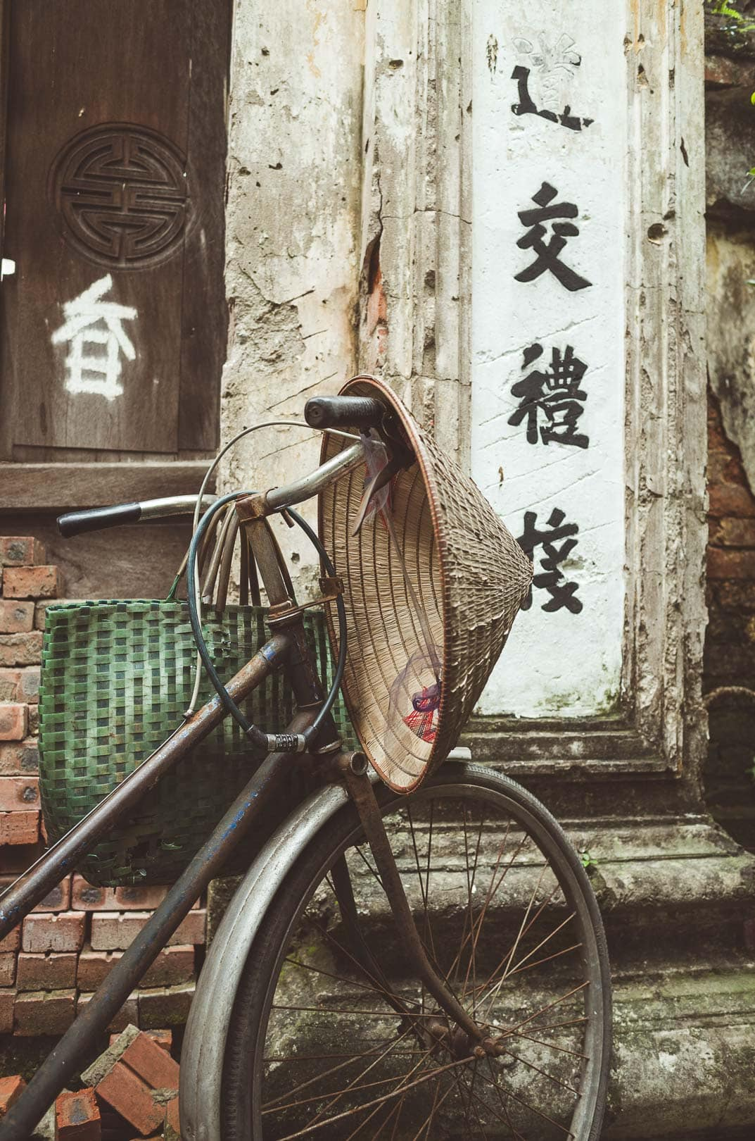 An Asian rice hat sits on a bike in Hanoi, Vietnam