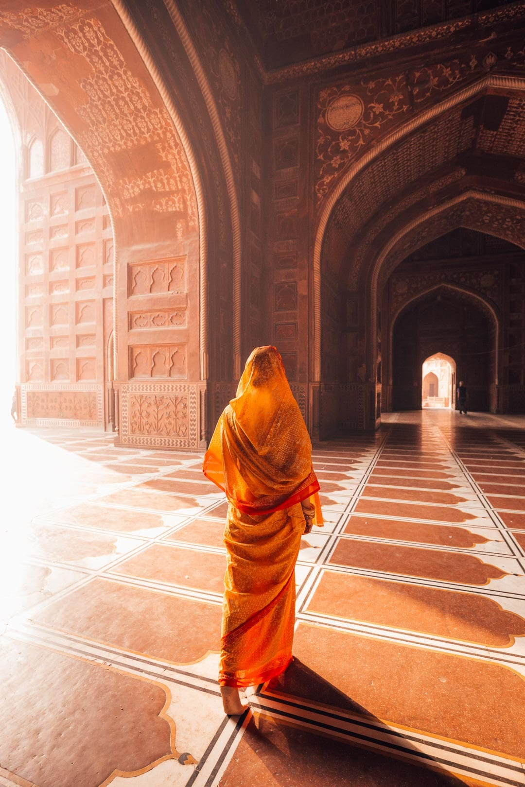A woman in an orange saree walks through the mosque.
