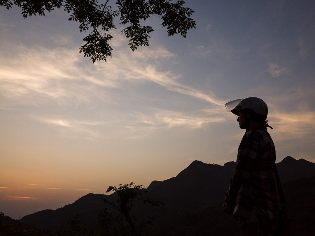 Silhouette of a motorcyclist in Ha Giang, Vietnam at sunset. How to ride the most epic motorcycle loop in Vietnam