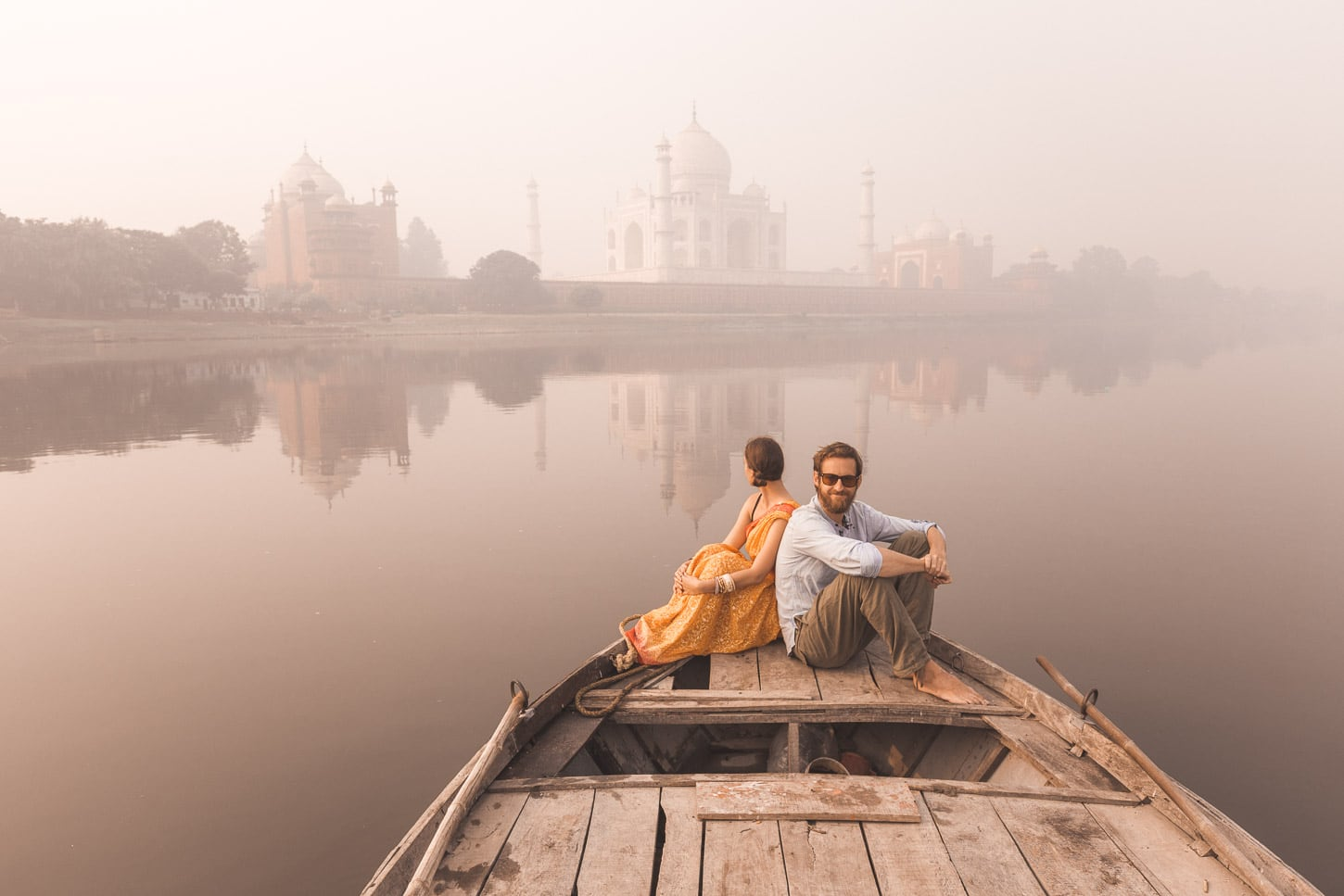 Travel couple Why We Seek on boat ride along the Yamuna River near the Taj Mahal