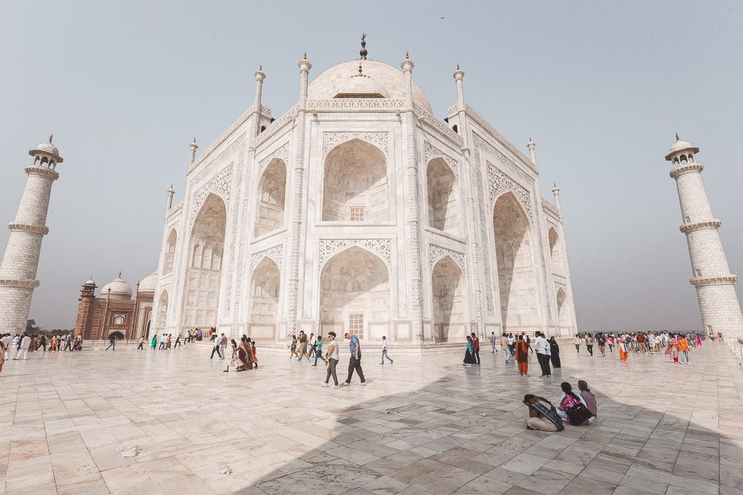 Corner view of the Taj Mahal with tourists walking on the main platform
