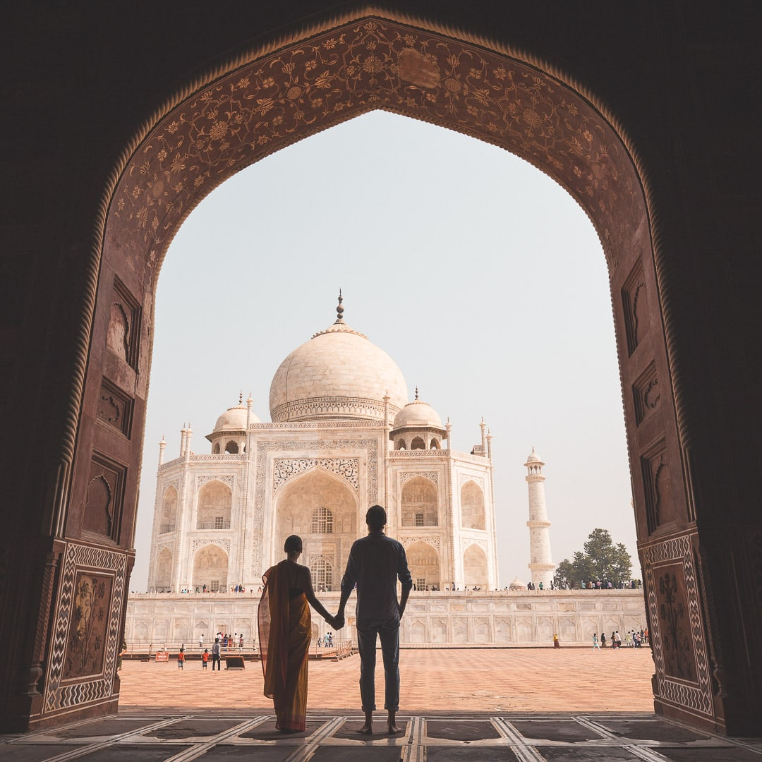 Silhouette of a couple holding hands admiring the Taj Mahal