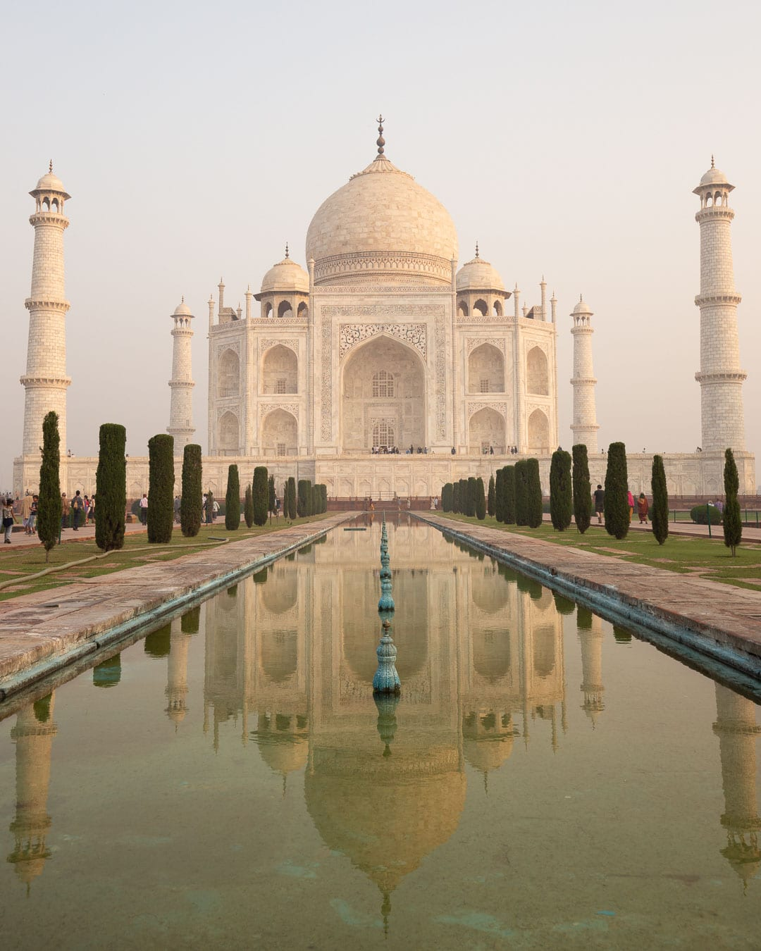 Early morning at the Taj Mahal with the monument reflecting in the fountain waters.