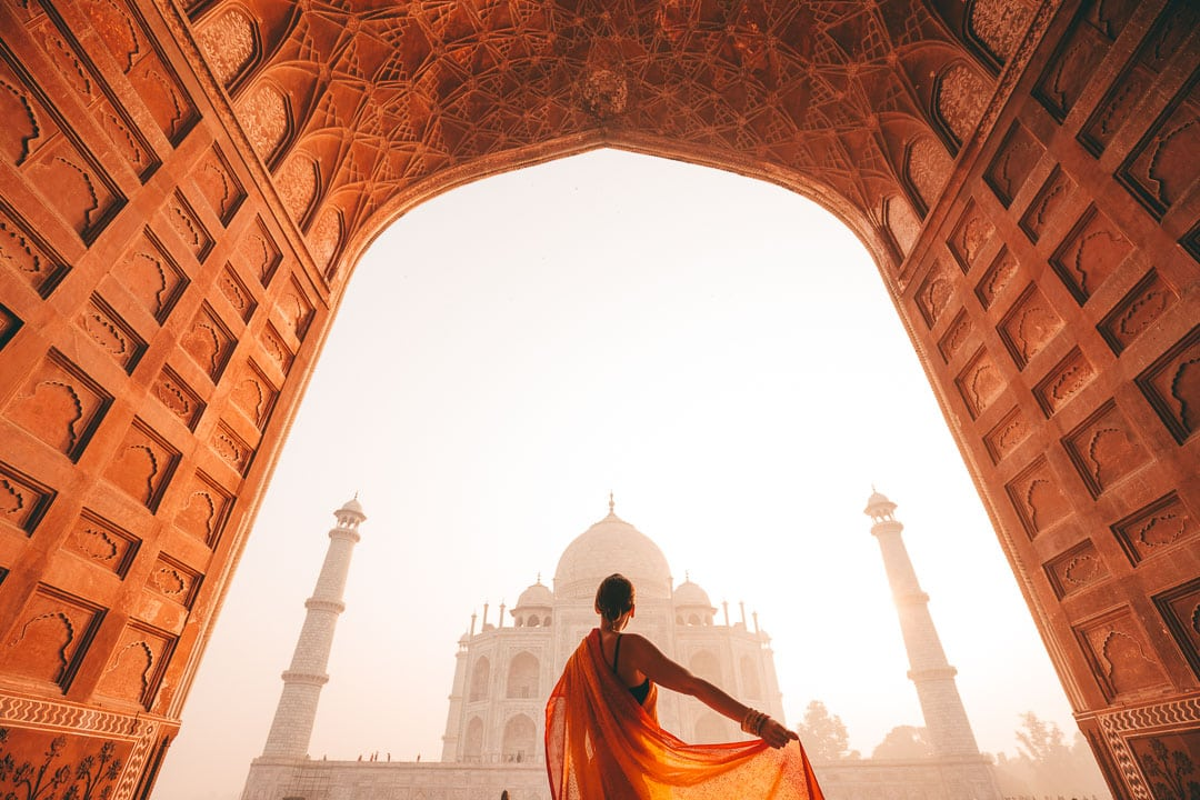 Sindhya holds her orange saree as she looks at the Taj Mahal at sunrise.