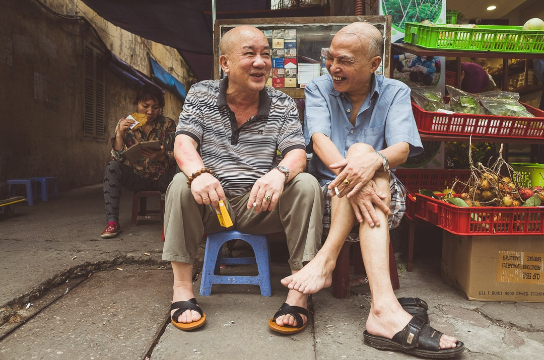 Two Hanoians share a laugh on small stools in front of a local store