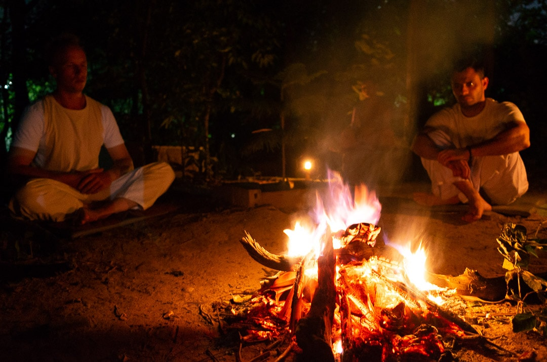 Two people meditate next to a campfire at Wat Umong temple in Chiang Mai, Thailand