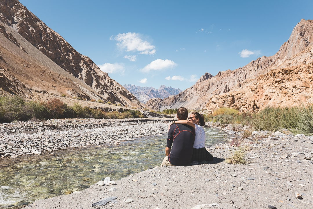 Why We Seek travel bloggers sit together near the Markha River in Ladakh, India
