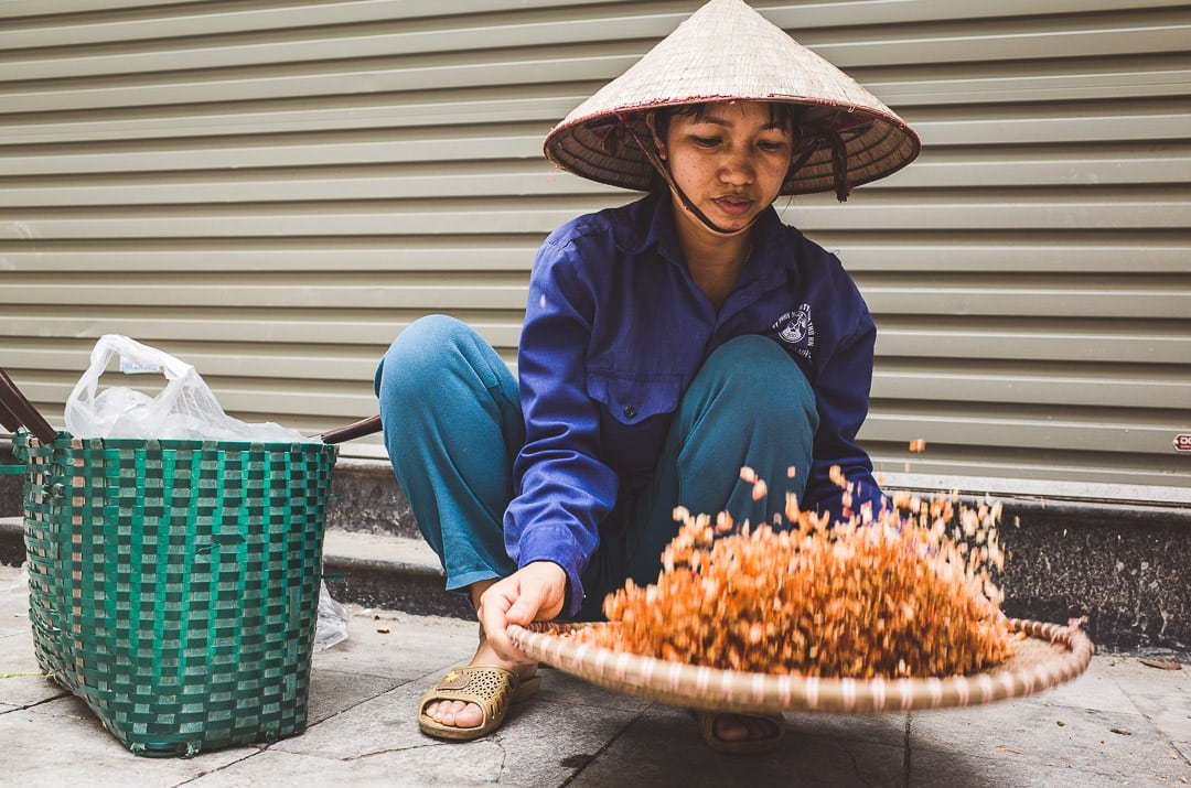 A local woman tosses dried shrimp in the Hanoi Old Quarter
