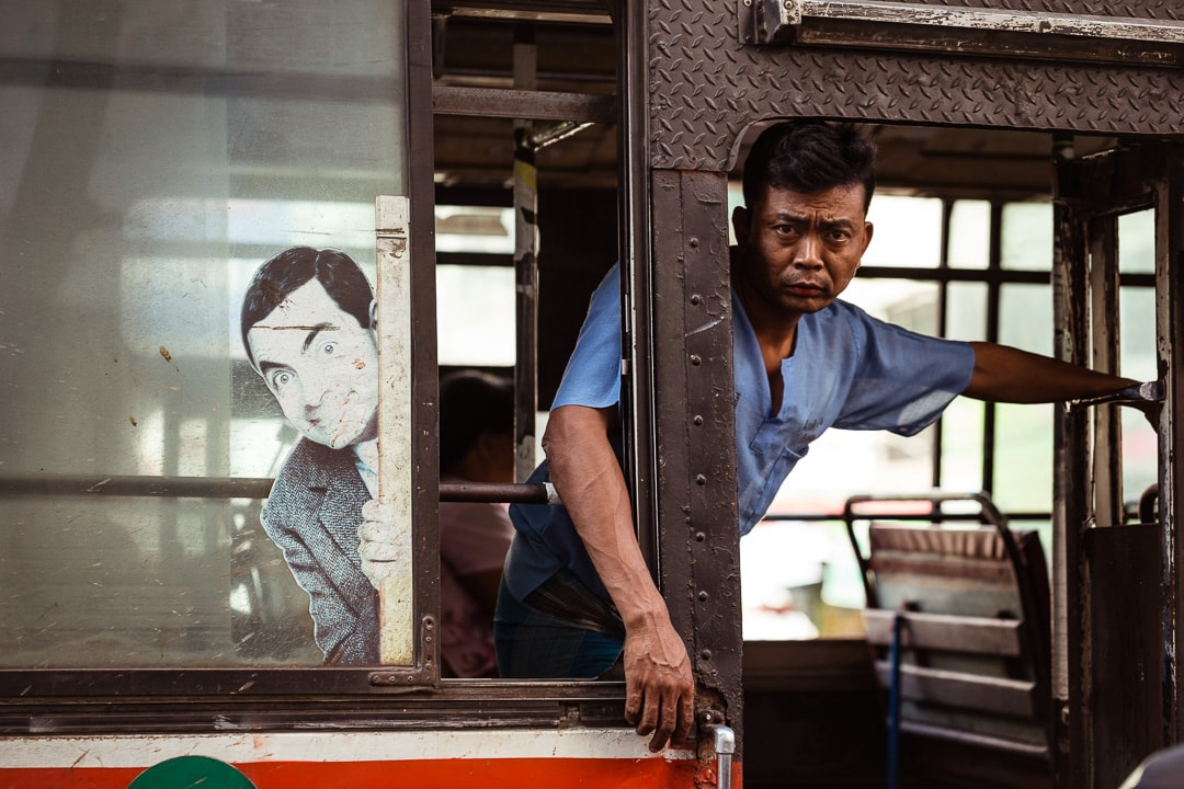 A local bus rider and Mr. Bean in Yangon