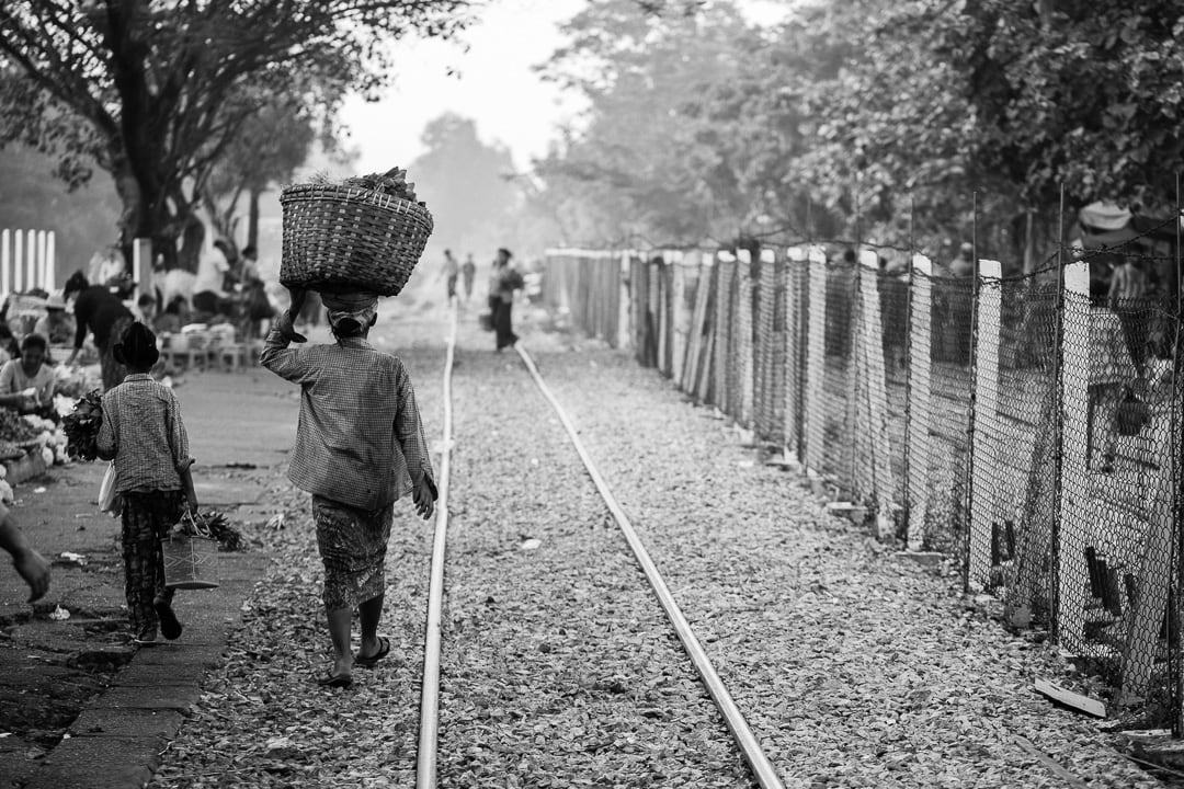A woman carries a basket near the tracks in Yangon