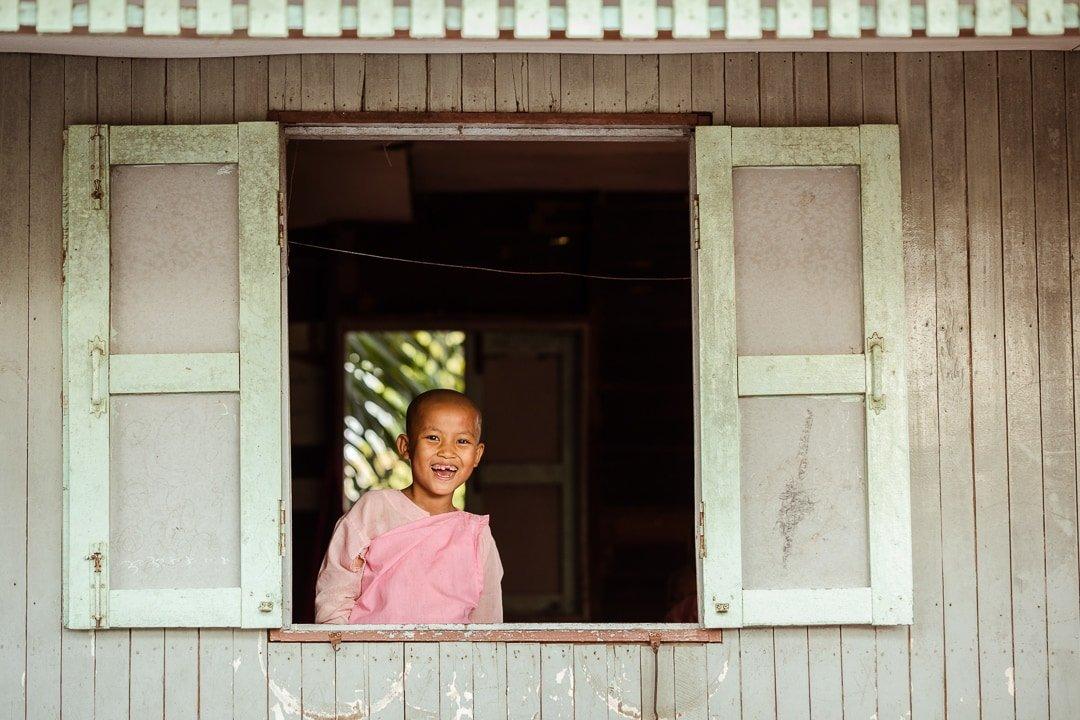 A young Buddhist nun smiles through a window in Burma