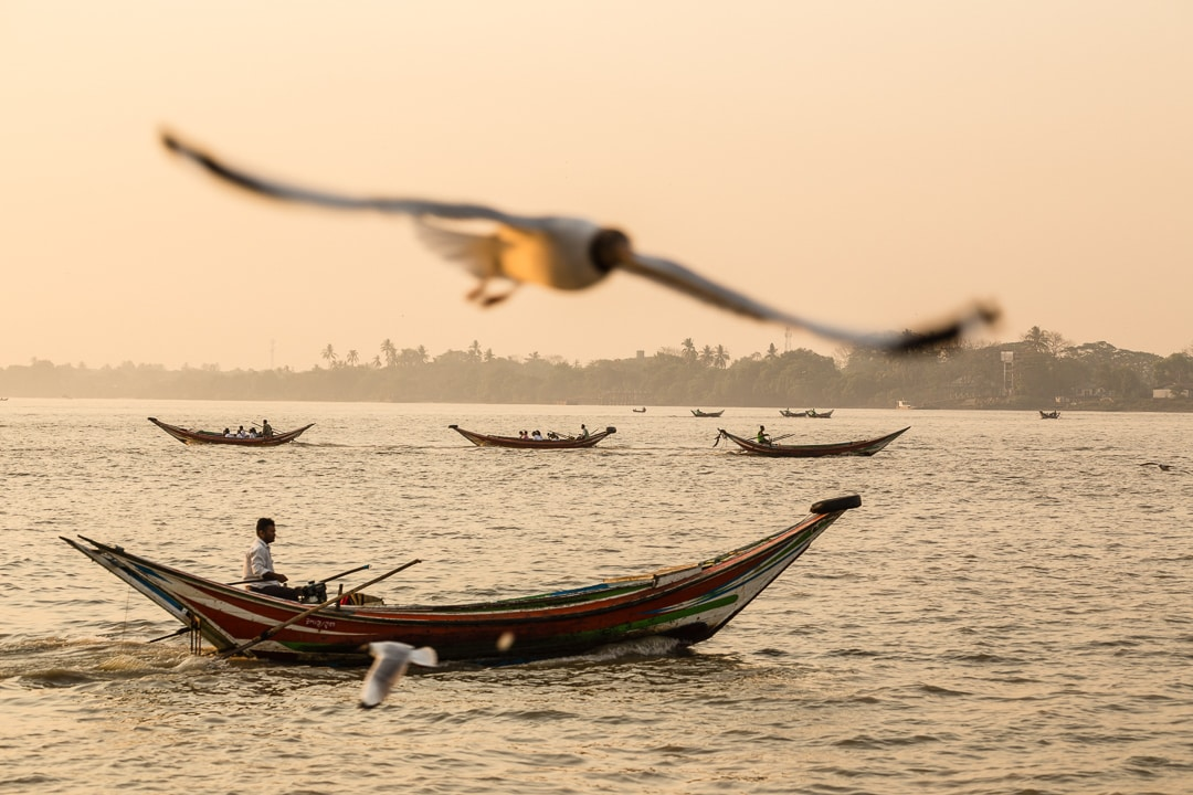 A man rows a boat on the Yangon River