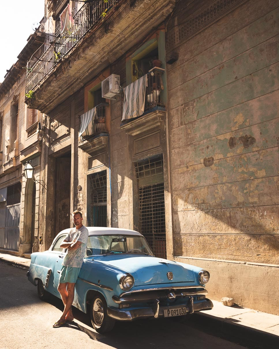 Matt leans against an old powder blue Chevy in Havana