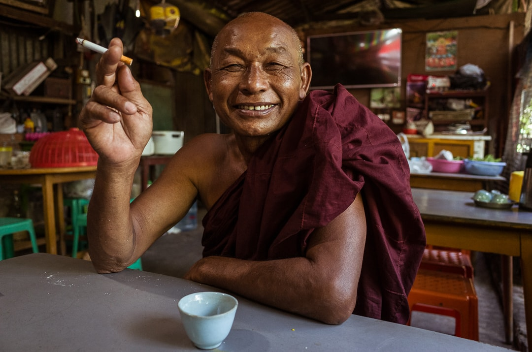 Portrait of a monk smoking a cigarette and drinking tea