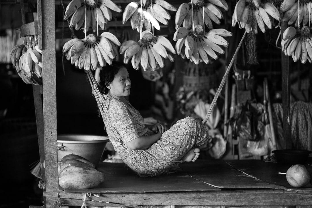 Woman in a hammock under bananas at Danyingon Market