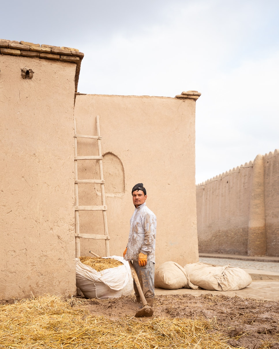 A laborer stands for a portrait while mixing mud and straw in Uzbekistan