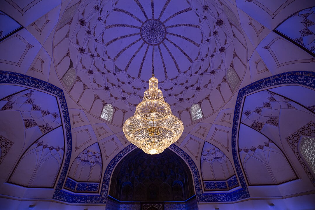 Chandelier hangs inside purple interior of Bolo Hauz Mosque