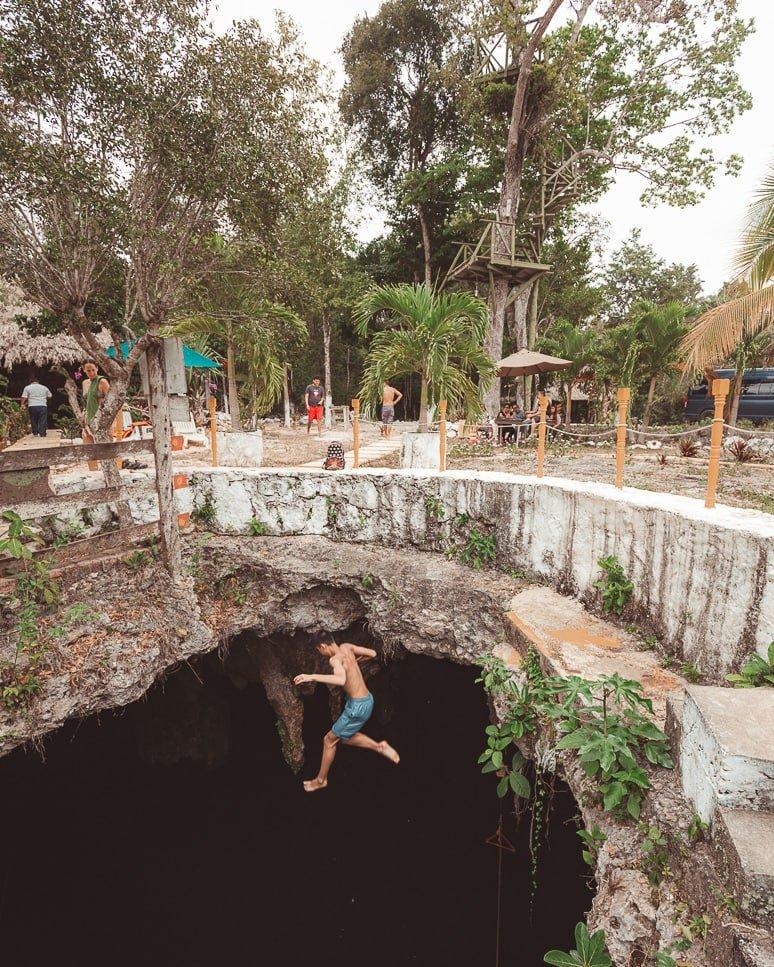 Man jumps into cenote la noria at ruta de los cenotes