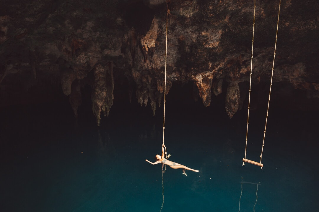 Sindhya floats on water inside Cenote La Noria one of the best cenotes in Cancun