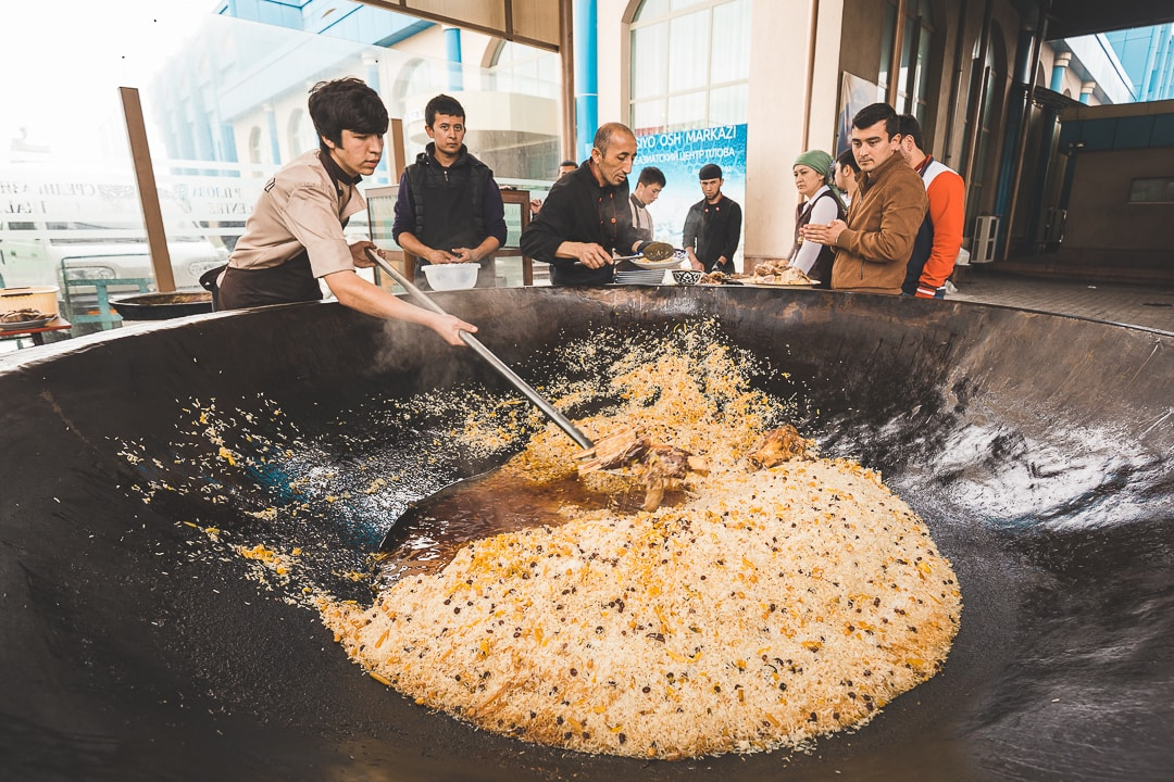 Man stirs a large cauldron of plov at the Central Asian Plov Center