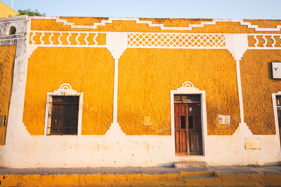 Wooden door and window on yellow wall with white trim in Izamal