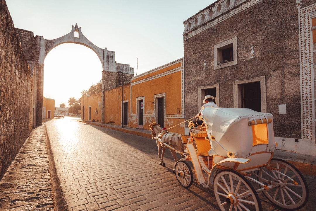 Horse drawn carriage going down cobblestone street as the sun sets in Izamal
