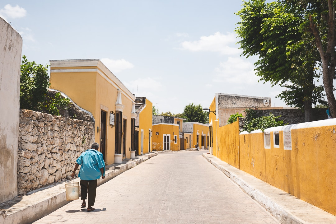 Man in a blue shirt walks down a street lined by yellow buildings in Izamal