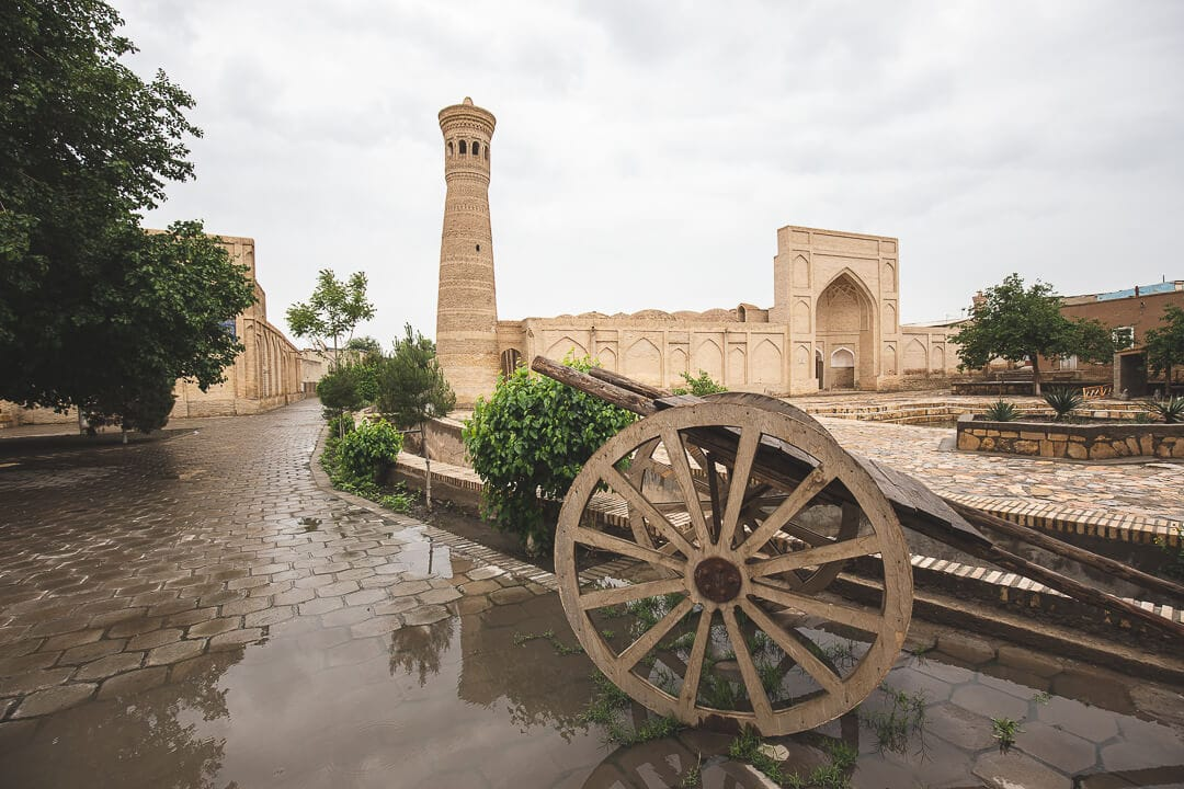 Minaret and wooden cart in a courtyard in Bukhara