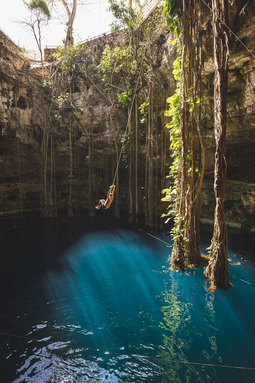 Matt swings on the rope swing into Cenote Oxman