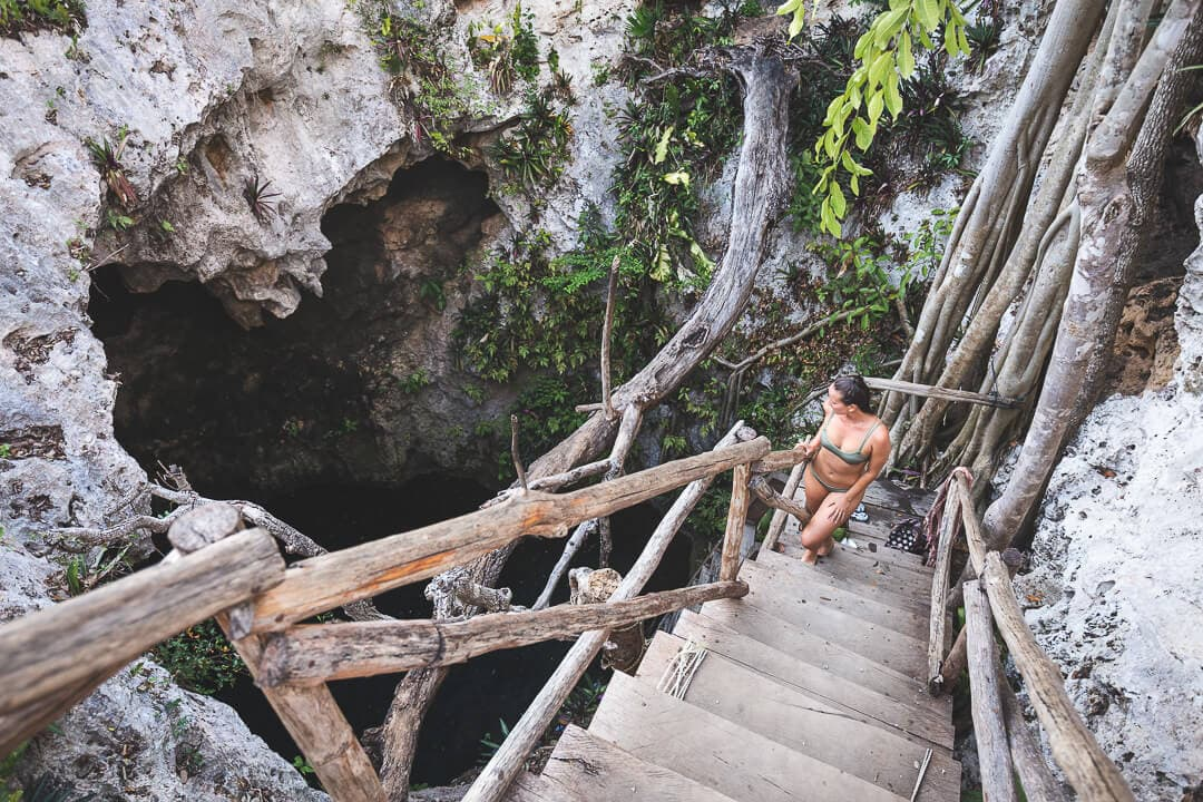 Sindhya stands on a wooden staircase and looks at Tres Oches cenote below
