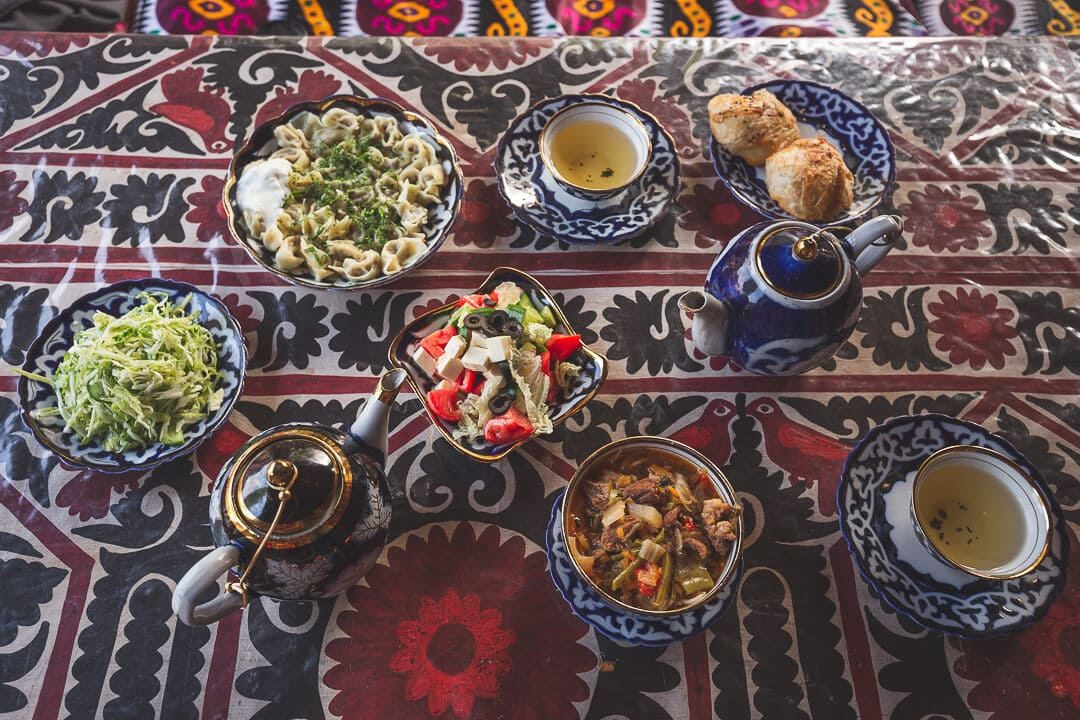 Spread of food and tea on top of a colorful suzani at Bibi Khanym teahouse. Travel guide to Samarkand.