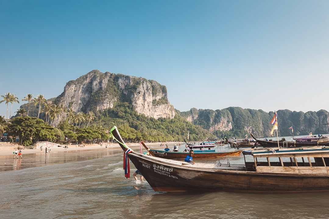 Long tail boats sit along shore of Ao Nang beach in Krabi